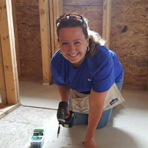 woman smiling holding a drill inside a new home