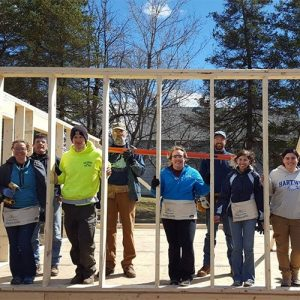 group of students standing between studs of a newly constructed wall