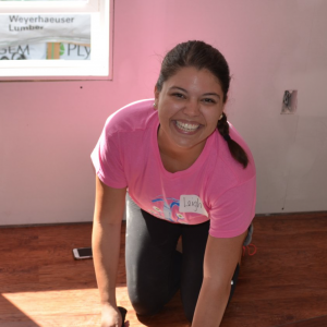 woman wearing pink in home with hammer smiling