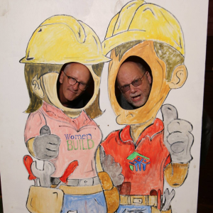two men with their faces in holes of a wooden cutout drawing of a woman and man in hardhats